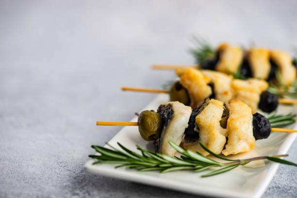 Barbecue fish skewers with olives and rosemary