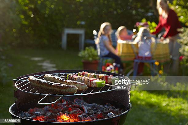 Barbecue grill on a summer evening with family in background