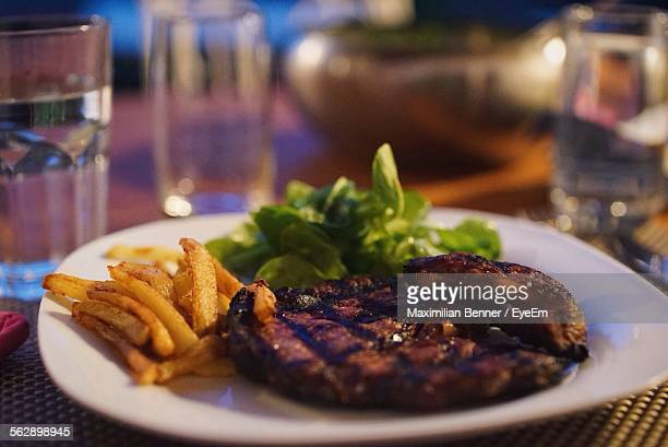 Barbecue Steak With French Fries And Lettuce In Plate On Table