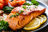 Barbecued salmon, fried potatoes and vegetables on wooden background