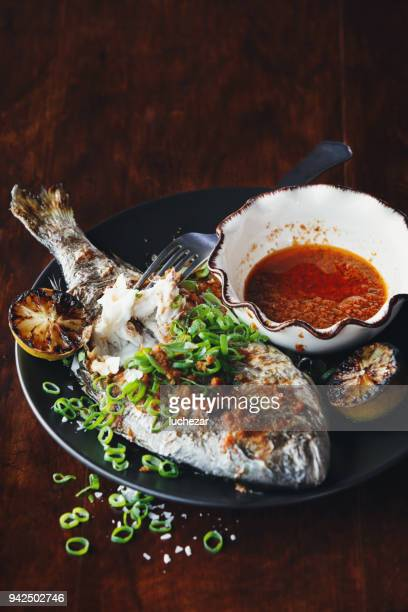 barbecued whole snapper with sauce - dorado fish stock photos and pictures