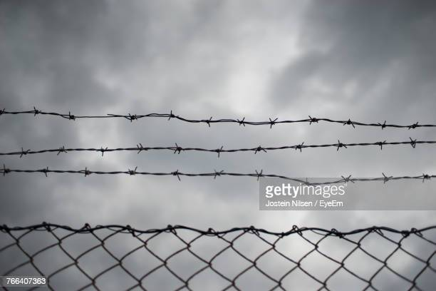 barbed wire against cloudy sky - barbed wire stock pictures, royalty-free photos & images