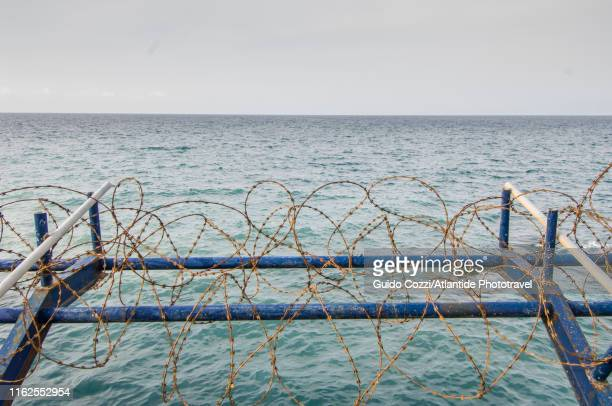 barbed wire along the corniche, seascape - image stock pictures, royalty-free photos & images