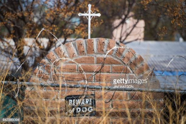 Barbed wire and a sign reading 'Beware of Dog' adorns a fence that backs up to the border fence in Nogales Arizona on February 17 on the US/Mexico...