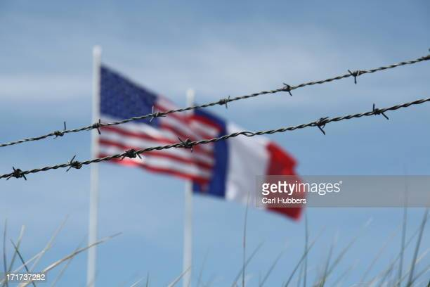 Barbed wire and American and French flags over Utah Beach, Normandy
