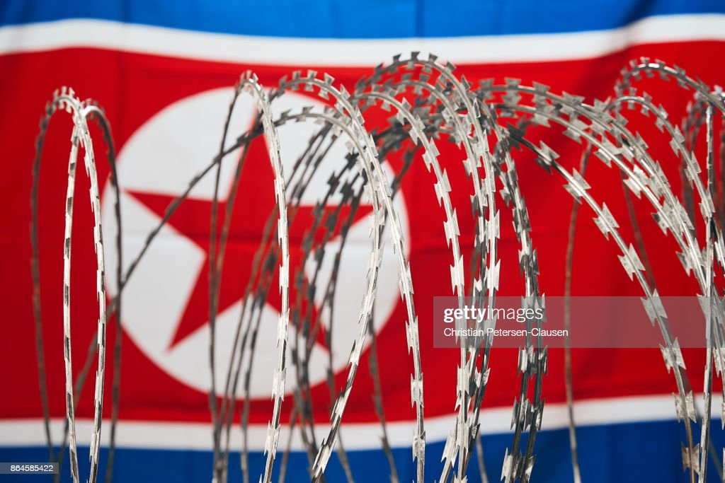 Barbed wire and North Korean national flag DPRK : Stock Photo
