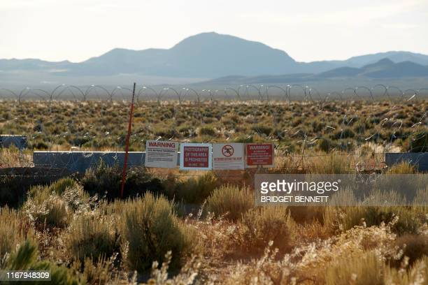 Barbed wire and signage border a gate of the Nevada Test and Training Range commonly referred to as Area 51 near Rachel Nevada on September 13 2019 A...