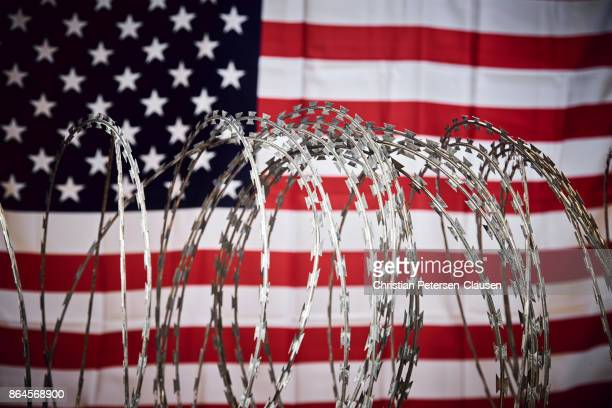 barbed wire and united states national flag - immigration stock pictures, royalty-free photos & images