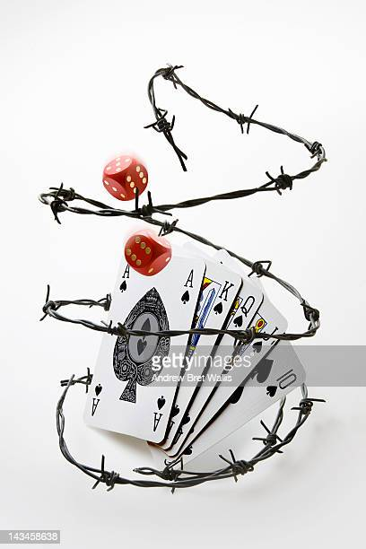 Barbed wire around playing cards and dice