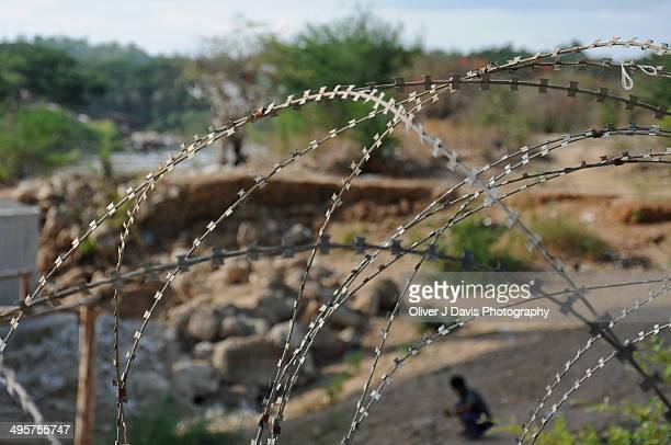 barbed wire fence at thailand - mae sot stock photos and pictures