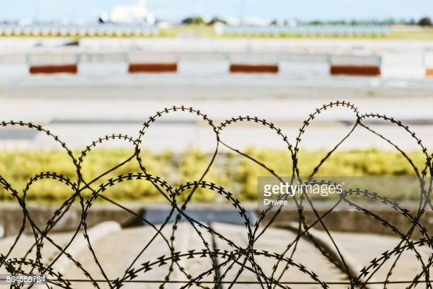 A Barbed Wire Fence Protecting The Airport Runways