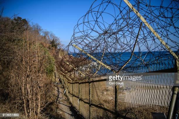 A barbed wire fence runs along a beach near the Korean Demilitarized Zone on February 3 2018 near Goseonggun South Korea The Demilitarized Zone runs...