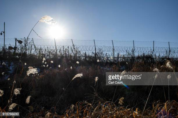 A barbed wire fence runs alongside the Han River near the Demilitarized Zone between South and North Korea on February 7 2018 near Panmunjom South...