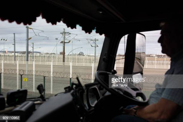 Barbed wire fencing is seen through the window as lorry driver Bob Evans sits waiting to board a freight train in Calais on March 6 2018 in Calais...