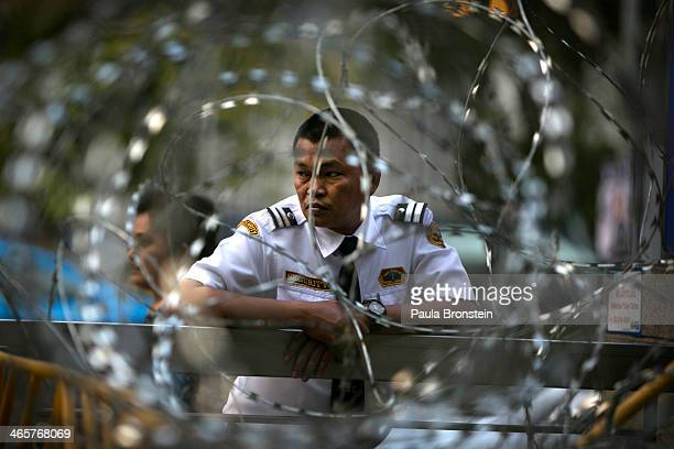 Barbed wire is seen as security stands guard outside the Pheu Thai party Yingluck Shinawatra's political party headquarters on January 29 2014 in...