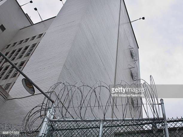 barbed wire on fence in prison, low angle view - prison building stock pictures, royalty-free photos & images