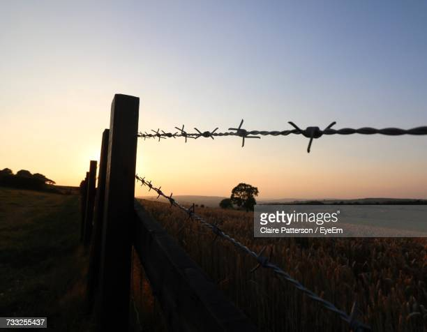 Barbed Wire On Field Against Sky During Sunset