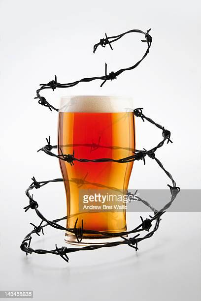 barbed wire surrounds a full beer glass - eingewickelt stock-fotos und bilder