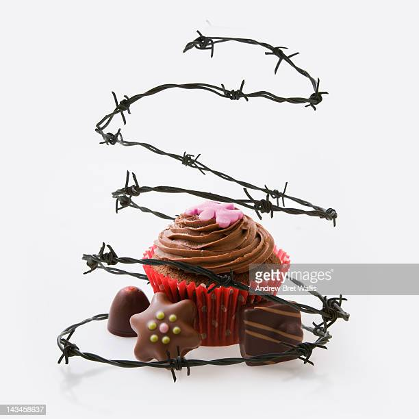 Barbed wire surrounds chocolate cake and candies