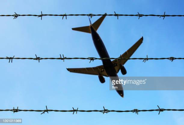 barbed wire with aircraft in the sky (schönefeld, brandenburg/ germany) - forbidden stock pictures, royalty-free photos & images