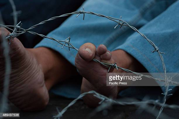 Barbed wired in front of a banner and feet Demonstration against borders and against the wall built in Hungary for the free circulation of people in...