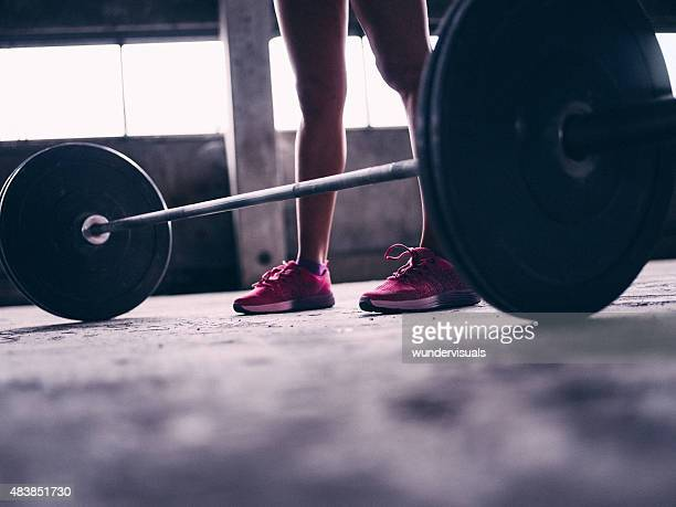 Barbell weights with a woman standing in pink sneakers
