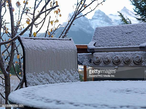 Barbeque and deck chairs dusted by first fall of autumn snow, mountains behind