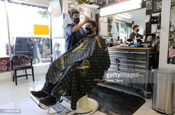Barber and his client wear face masks in the Hollywood Barber Shop shortly before closing amid new restrictions due to the COVID-19 pandemic on July...