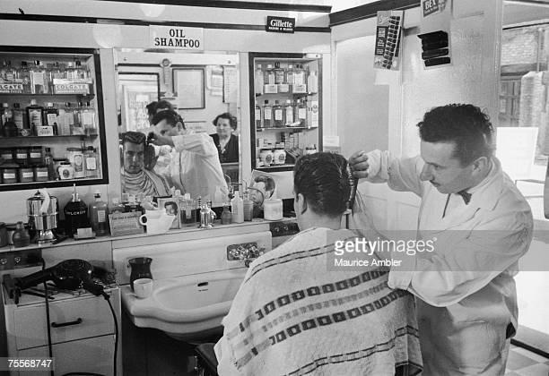 Barber Angel Rose sculpts a customer's hair into a DA style at his barber's shop in Tottenham Court Road London 13th November 1954 Original...