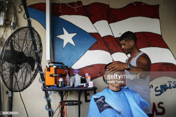 Barber Angel Ruben cuts Jimmy Ramirez Ortiz's hair outdoors in front of a painted Puerto Rican flag in an area without power about two weeks after...