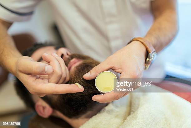 Barber applying cream on beard of a customer