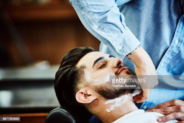 Barber applying shaving cream to clients face