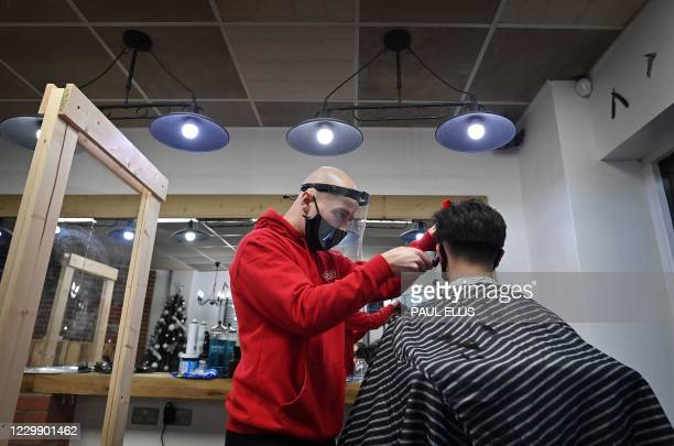 Barber Ben Fessey cuts the hair of his first customer after reopening his barber shop in Moreton, north west England, on December 2, 2020 as England...