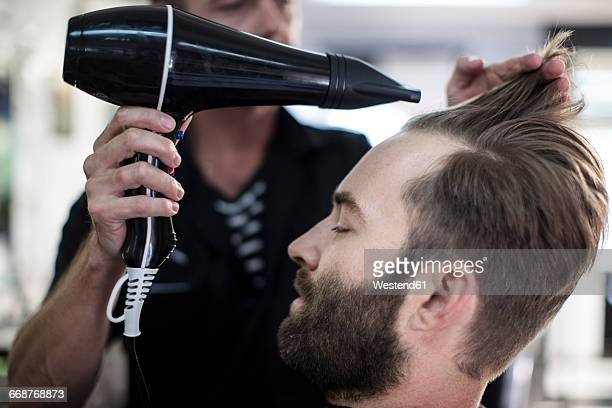 Barber blow-drying hair of a customer