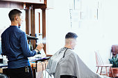 barber blowing water onto clients hair
