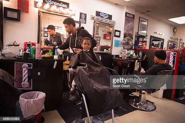 Barber Branden Turner cuts Deverain Word's hair at the Prime Time Barber and Beauty shop on West Florissant Street November 15 2014 in Ferguson...