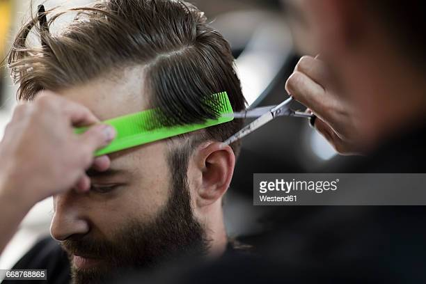 Barber combing and cutting hair of a customer