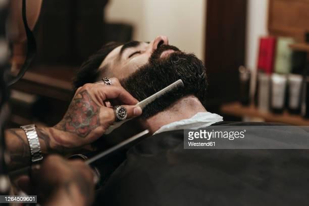 barber combing client's beard at salon - männer über 30 stock-fotos und bilder