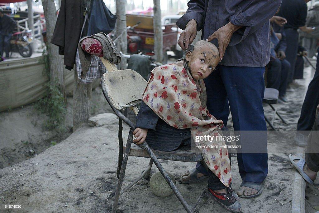 barber cuts a boy's hair in Khotan, China. : Bildbanksbilder