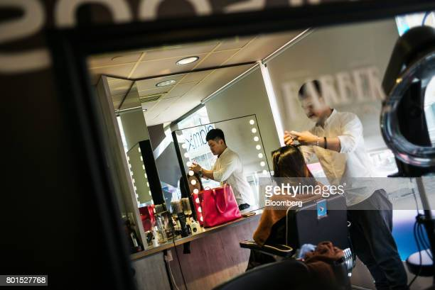 A barber cuts a customer's hair inside a Watsons store operated by AS Watson Group a unit of CK Hutchison Holdings Ltd in the Causeway Bay district...