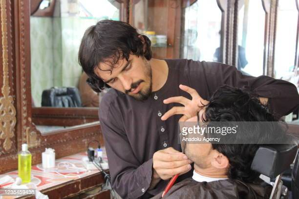 Barber cuts shaves beard at a shop in Khost, Afghanistan on September 23, 2021. Barbers in Afghanistan's Khost province say, with the advent of the...
