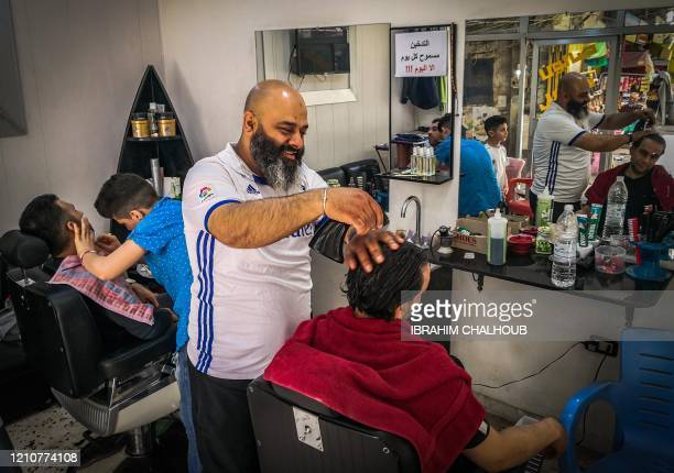 A barber cuts the hair of a client while his child assistant trims the beard of another at their shop on the Abu alFoz street mainly inhabited by...