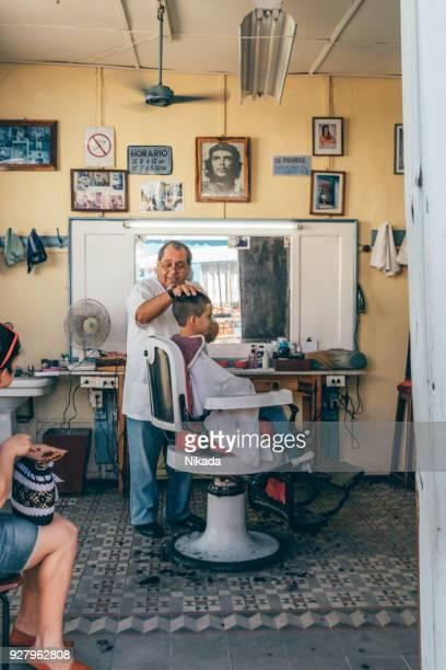 Friseur Haare schneiden eines kleinen Jungen in einem kleinen Friseursalon