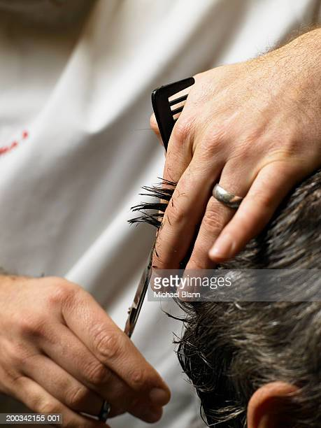 Barber cutting man's hair, close-up of hands