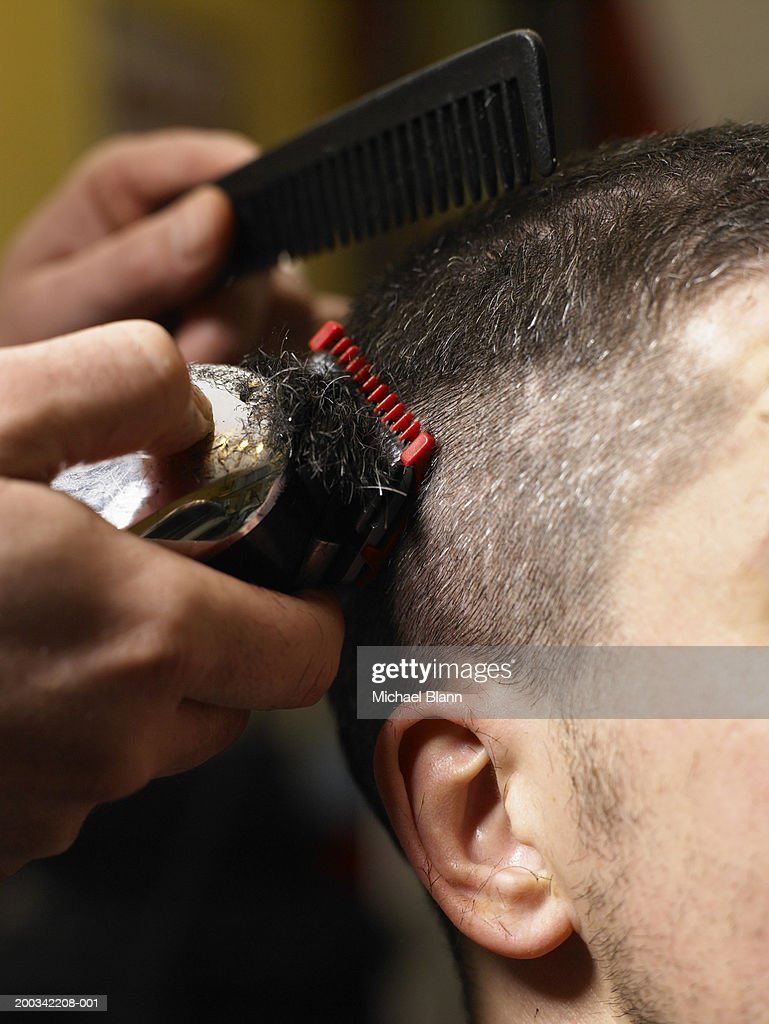 Barber cutting man's hair with electric razor, close-up of hands : Stock Photo