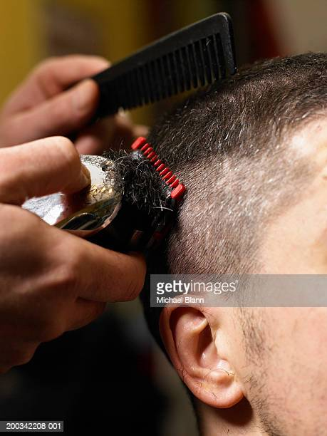 Barber cutting man's hair with electric razor, close-up of hands