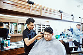 barber cutting mans hair with trimmer