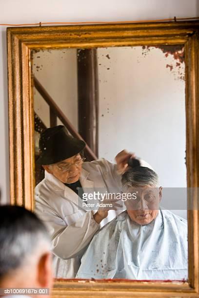 Barber cutting senior man's hair