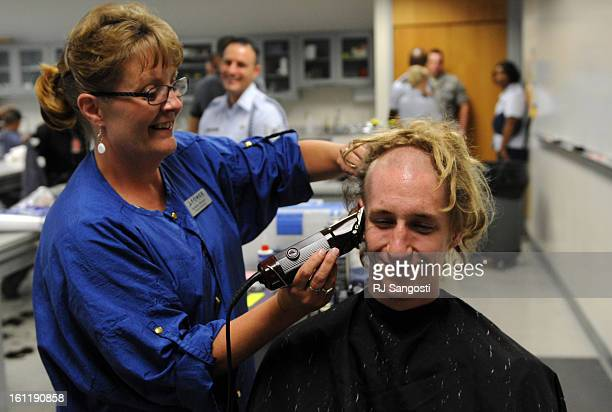 Barber Debbie Vinson shaves the dreadlocks off the head of Alex Hooks of Las Cruces New Mexico as the class of 2015 recruits check in Thursday June...