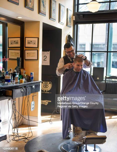 Barber Gabe Luevano left of Barbeer Cut and Beer cuts the hair of client Edgar Mendoza of Buena Park Barbeer is one of the businesses in the Center...